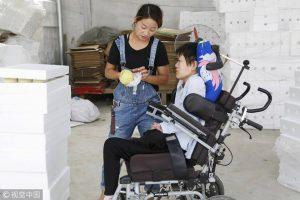 Tanara din China care conduce o afacere online desi este paralizata examineaza marfa