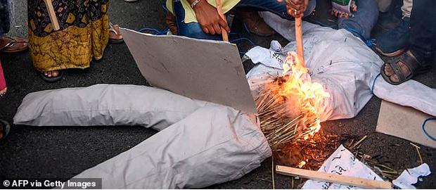 Demonstranții ard o păpușă de paie a violatorului cerând dreptate