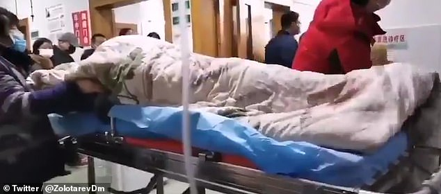 Pacient zvârcolindu-se incontrolabil pe un cărucior de spital în Wuhan